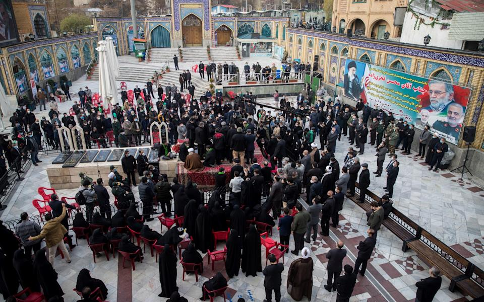 Mourners attend the burial ceremony of Iranian nuclear scientist Mohsen Fakhrizadeh at the shrine of Imamzadeh Saleh, in Tehran - WANA News Agency/Reuters