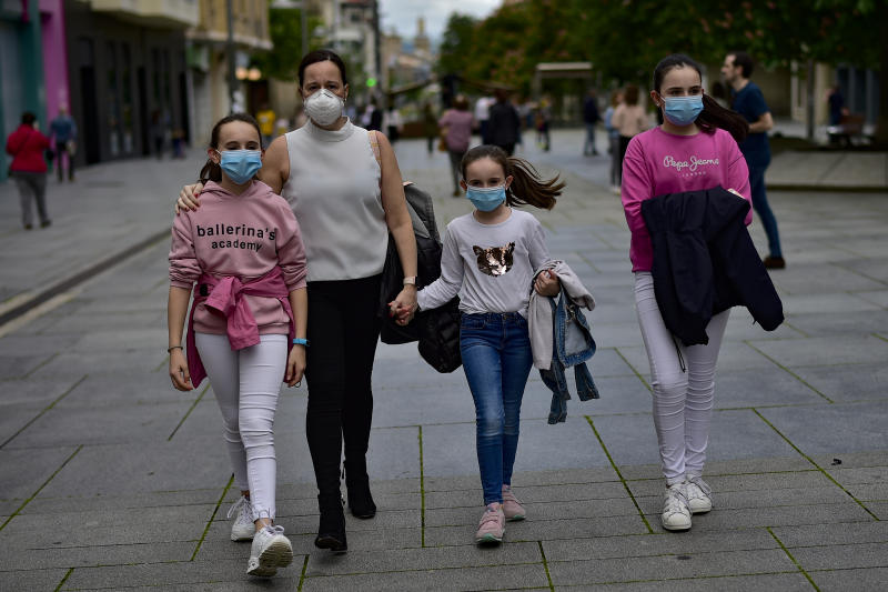 A family wearing face mask to protect of the coronavirus go for a walk at Carlos III promenade, in Pamplona, northern Spain, Sunday, April 27, 2020. On Sunday, children under 14 years old will be allowed to take walks with a parent for up to one hour and within one kilometer from home, ending six weeks of compete seclusion. (AP Photo/Alvaro Barrientos)
