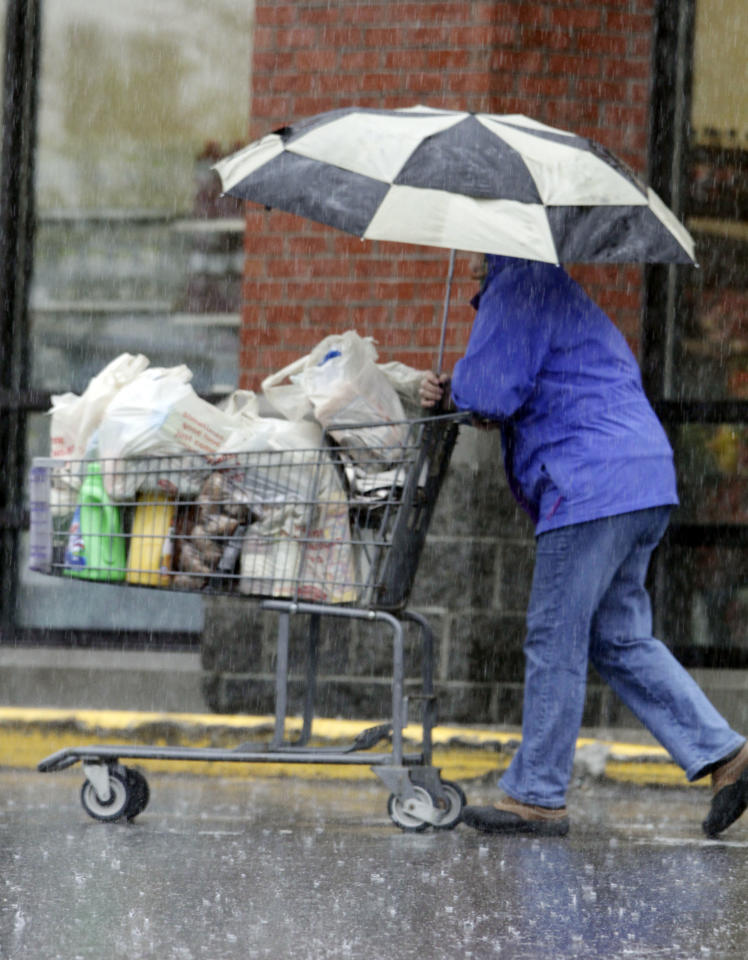 A shopper braves heavy rain while leaving a grocery store in Brunswick, Maine on Monday, April 23, 2012. The state is receiving its first major rain storm during the month of April. A spring nor'easter packing soaking rain and high winds churned up the Northeast Monday morning, unleashing a burst of winter and up to a foot of snow in higher elevations inland, closing some schools and sparking concerns of power outages. (AP Photo/Pat Wellenbach)