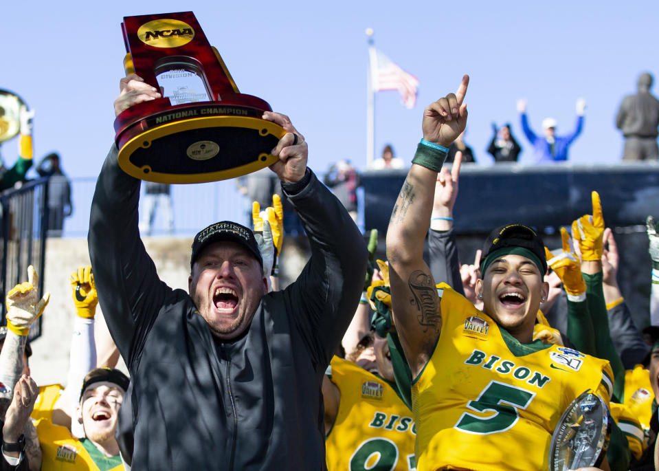 FILE - In this Jan. 11, 2020, file photo, North Dakota State head coach Matt Entz raises the trophy alongside quarterback Trey Lance (5) as they celebrate after beating James Madison 28-20 in the FCS championship NCAA college football game in Frisco, Texas. The Football Championship Subdivision season begins in earnest this weekend. With the fall season and playoffs, some of the top teams could play as many as two dozen games over a calendar year. Health experts say players face immense physical and mental challenges playing so many games.(AP Photo/Sam Hodde, File)