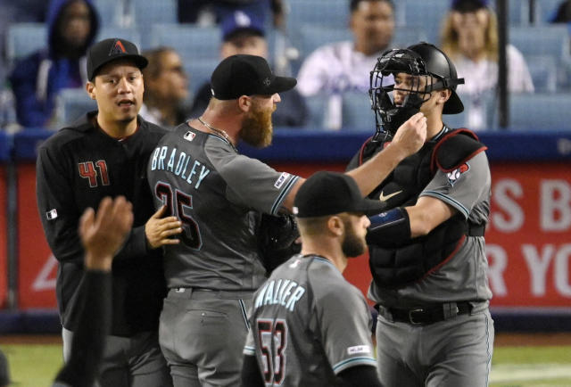 Arizona Diamondbacks' Archie Bradley, second from left, gestures toward the Los Angeles Dodgers' dugout as he is held back by Wilmer Flores, left, and catcher Carson Kelly, right, after the Diamondbacks defeated the Dodgers 3-2 in a baseball game Friday, Aug. 9, 2019, in Los Angeles. (AP Photo/Mark J. Terrill)