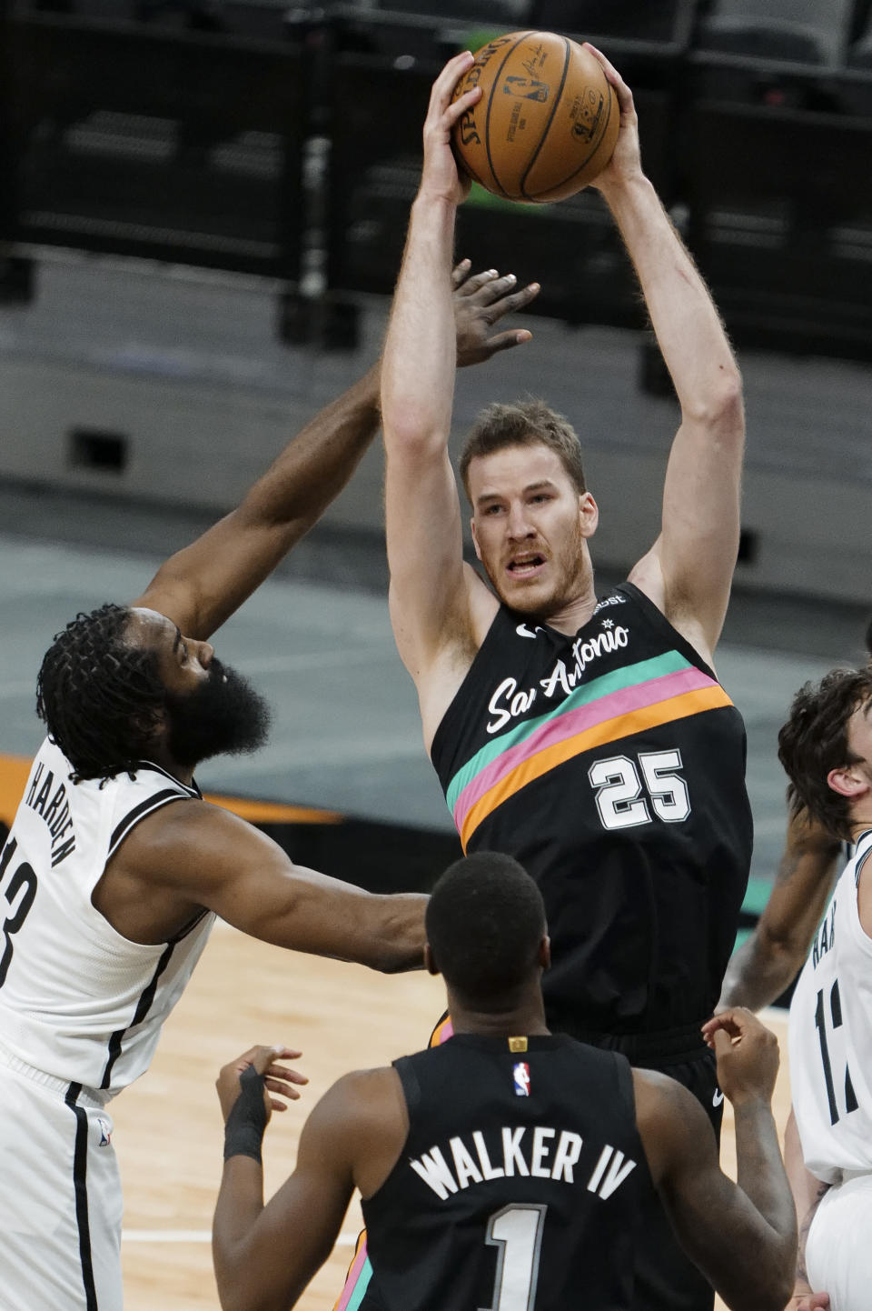 San Antonio Spurs' Jakob Poeltl (25) fights for the rebound against Brooklyn Nets' James Harden, left, during the first half of an NBA basketball game, Monday, March 1, 2021, in San Antonio. (AP Photo/Darren Abate)