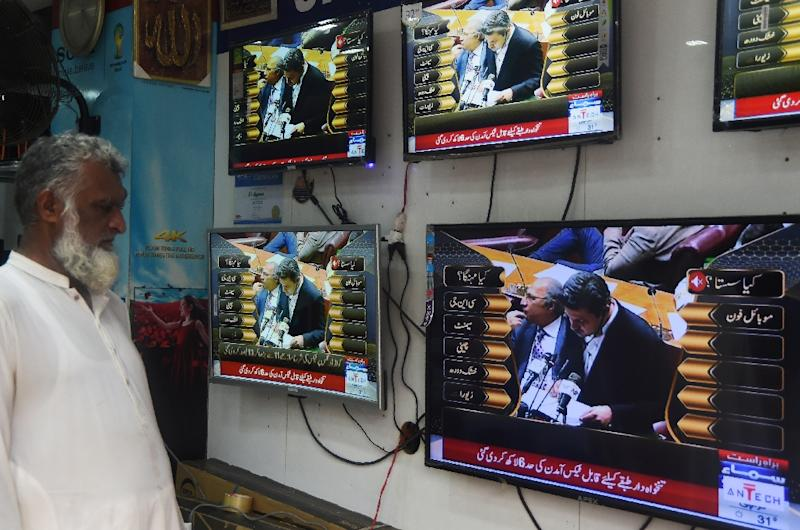 A Pakistani shopkeeper in Karachi watches a television broadcast of Pakistan's Minister of State for Revenue Hammad Azhar presenting the state budget for the year 2019-20 at parliament in Islamabad (AFP Photo/ASIF HASSAN)