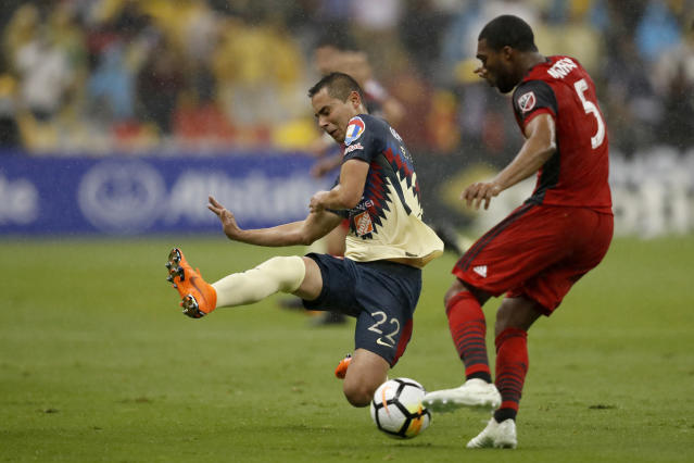 Paul Aguilar of Mexico's America, left, and Ashton Morgan of Canada's Toronto FC fight for the ball during the second leg of a CONCACAF Champions League soccer semifinal in Mexico City, Tuesday, April 10, 2018. (AP Photo/Eduardo Verdugo)