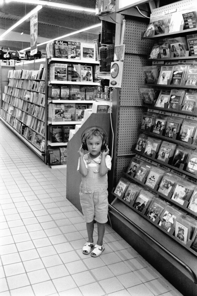 <p>A young girl dons a giant pair of headphones as she listens to album previews in the CD section at the supermarket.</p>