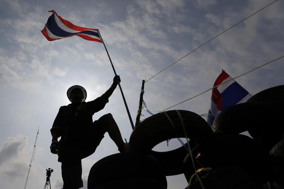 An anti-government protester holds a flag on a barricade as policemen gather in front of it near the Government House in Bangkok February 18, 2014. A Thai police officer was killed and dozens of police and anti-government protesters were wounded in gun battles and clashes in Bangkok on Tuesday, officials and witnesses said. REUTERS/Damir Sagolj (THAILAND - Tags: SOCIETY CIVIL UNREST POLITICS)