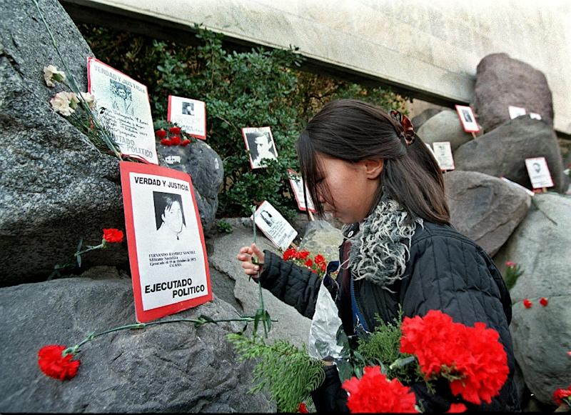 A relative of the Caravan of Death incident places flowers in the Memorial to the Detained and Disappeared at the Santiago cemetery, on July 21, 1999