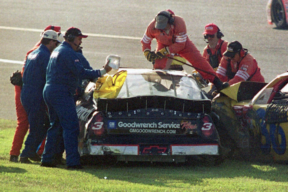 FILE - In this Feb. 18, 2001, file photo, workers try to remove Dale Earnhardt (3) from his vehicle after a crash also involving Ken Schrader (36) during the NASCAR Daytona 500 auto race at the Daytona International Speedway in Daytona Beach, Fla. Since its widespread introduction two decades ago, sparked by the stunning death of seven-time NASCAR champion Dale Earnhardt on the final lap of the 2001 Daytona 500, the HANS device has become a standard piece of safety equipment in pretty much all forms of racing. (AP Photo/Greg Suvino, File)