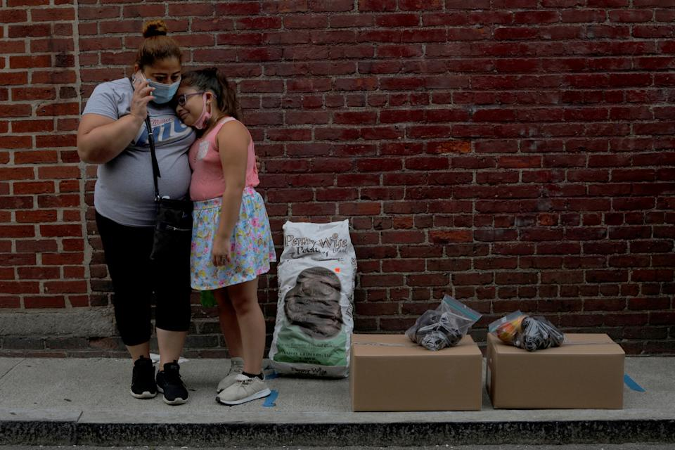 Sandra Cruz, who lost her job because of the coronavirus disease (COVID-19) outbreak, and fell four months behind on her rent and is fearing eviction, and her daughter Gabriella wait for a ride after picking up free groceries distributed by the Chelsea Collaborative in Chelsea, Massachusetts, U.S., July 22, 2020.   REUTERS/Brian Snyder     TPX IMAGES OF THE DAY