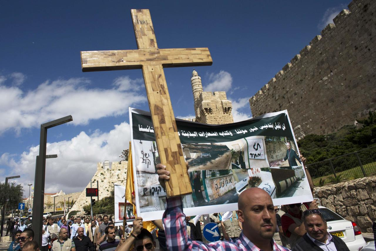 A Palestinian protester holds a cross during a demonstration against acts of vandalism on Christian sites in Israel and the occupied West Bank, outside Jerusalem's Old City October 6, 2013. Last week four suspected Jewish nationalists were arrested for smashing headstones in a Christian cemetery near Jerusalem's walled Old City. REUTERS/Ronen Zvulun (JERUSALEM - Tags: RELIGION POLITICS)