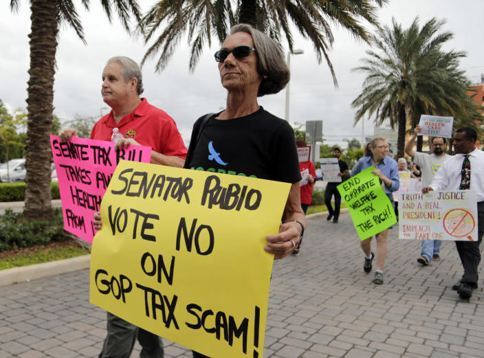 <p>Fred Frost, left, and Deborah Dion, right, protest against a Republican tax bill outside of the office of Sen. Marco Rubio, R-Fla., Monday, Nov. 27, 2017, in Doral, Fla. (Photo: Lynne Sladky/AP) </p>