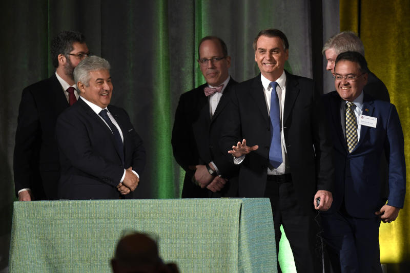 Brazilian President Jair Bolsonaro, center, waves as he goes over to meet those involved in a signing ceremony at the Chamber of Commerce in Washington, Monday, March 18, 2019. (AP Photo/Susan Walsh)