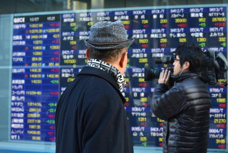 People pass an electronic share price board in Tokyo on December 27, 2012