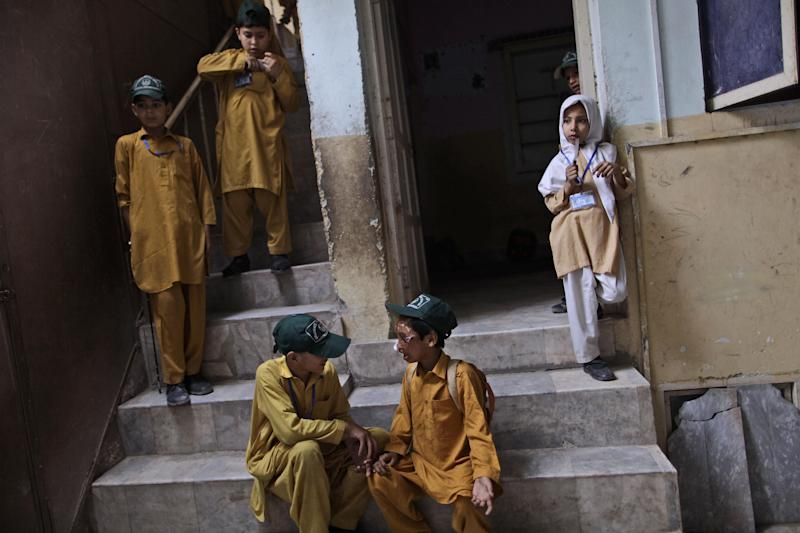 """In this Friday, May 25, 2012 photo, Pakistani acid Attack survivor Akhtar Yar, 9, bottom right, talks with his classmate Abduallah about his medical trip to Islamabad, at his school yard in Peshawar, Pakistan. Akhtar and his father were attacked in 2004 by a man whose the father had an argument with earlier in the day. The nose has special significance in Pakistani culture, where it symbolizes the honor of the family. A popular plea from parents to children is """"Please take care of our nose"""", which means """"don't do anything that tarnishes the name of the family."""" (AP Photo/Muhammed Muheisen)"""