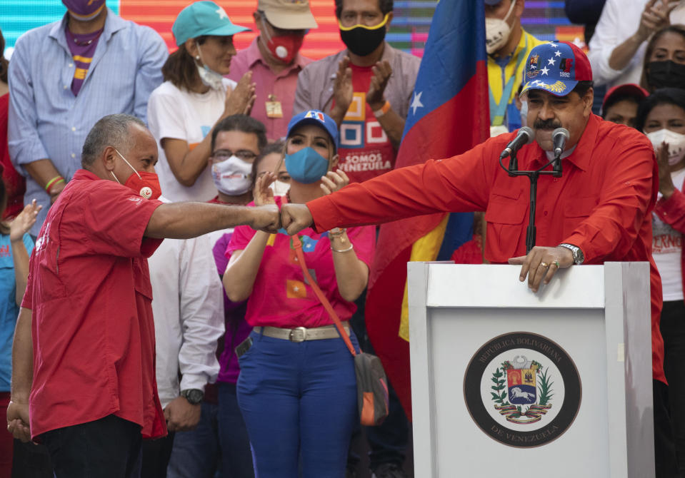Diosdado Cabello, a candidate for Monagas state for the Great Patriotic Pole party in the upcoming National Assembly elections, left, bump fists with Venezuela's President Nicolas Maduro during a closing campaign rally in Caracas, Venezuela, Thursday, Dec. 3, 2020. Venezuelans will vote for a new National Assembly on Sunday, Dec 6. (AP Photo/Ariana Cubillos)