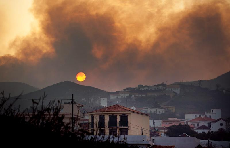 Smoke billows across houses as a wildfire burns near Chipude Village, La Gomera, Spain, Sunday, Aug. 12, 2012.  Wildfires spurred by high temperatures raged across Spain's Canary Islands of La Gomera and Tenerife as well as Ourense in northwestern Spain. Flames are threatening some of Europe's oldest surviving forests in the Garajonay National Park in La Gomera and have forced the evacuation of hundreds of people across the country. (AP Photo/Andres Gutierrez)
