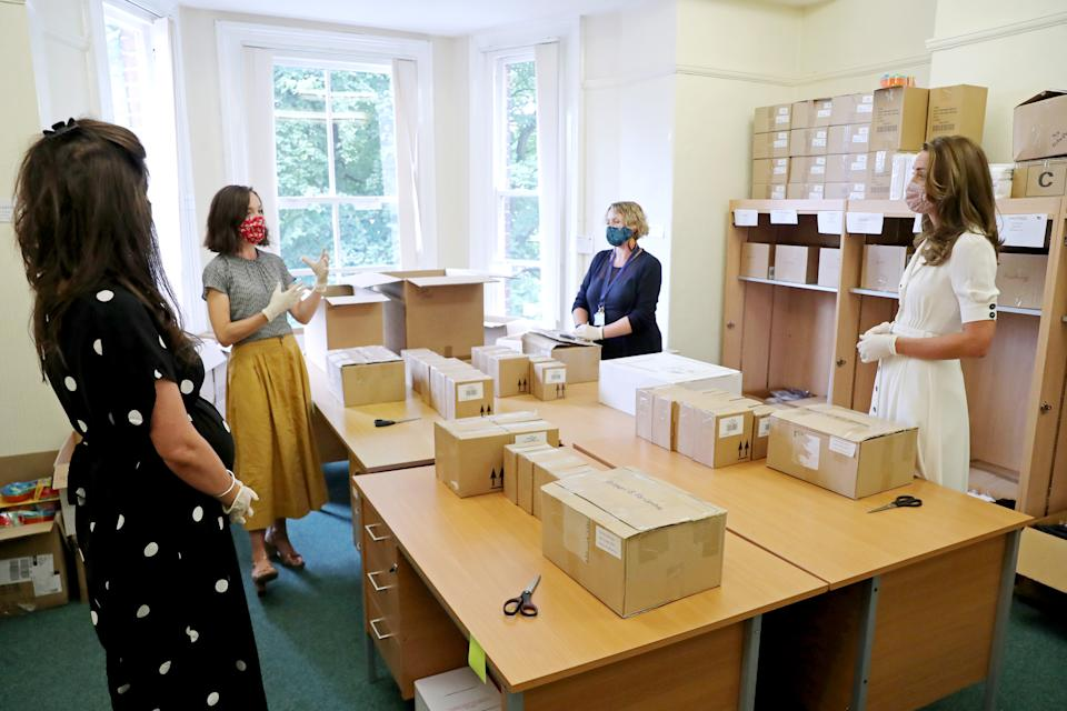 Britain's Catherine, Duchess of Cambridge wears a face mask or covering and gloves due to the COVID-19 pandemic, helps unpack supplies during her visit to a baby bank in Sheffield, northern England on August 4, 2020. - Baby banks aim to support and empower families by ensuring every child has the essential items they need to thrive. In the UK, they are powered primarily by volunteers and typically run on professional referral from services such as health visitors, midwives and social workers. (Photo by Chris Jackson / POOL / AFP) (Photo by CHRIS JACKSON/POOL/AFP via Getty Images)
