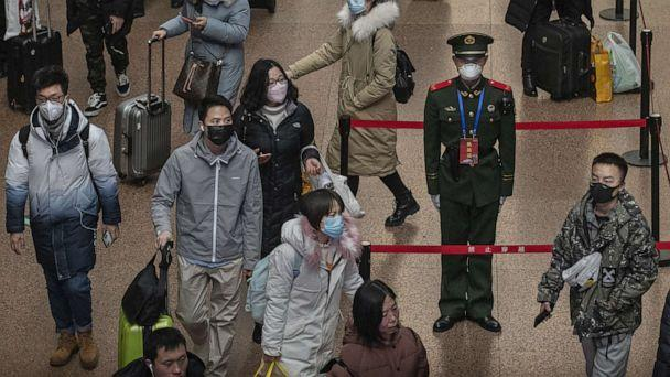 PHOTO: A Chinese police officer wears a protective mask as passengers, many wearing masks also, arrive to board trains before the annual Spring Festival at a Beijing railway station in Beijing, Jan. 23, 2020. (Kevin Frayer/Getty Images, FILE)
