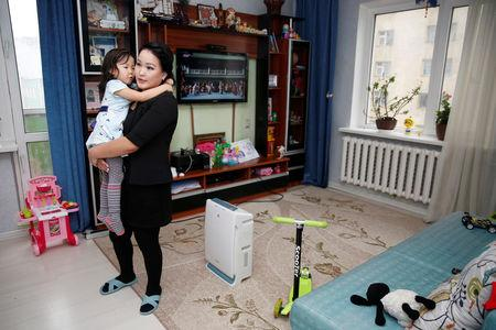 Mandakhjargal Tumur, coordinator at the non-governmental organization (NGO) Moms and Dads Against Smog, holds her 4-year-old daughter at her living room in Ulaanbaatar, Mongolia February 1, 2019. Picture taken February 1, 2019. REUTERS/B. Rentsendorj