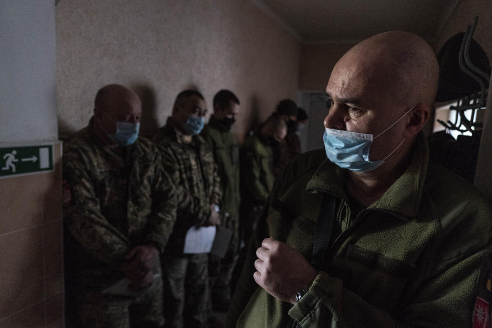 Ukrainian servicemen wait to receive a dose of the AstraZeneca COVID-19 vaccine marketed under the name CoviShield at a military base in Kramatorsk, Ukraine, Tuesday, March 2, 2021. Ukraine plans to vaccinate 14.4 million people this year, or about 35% of its 41 million people. (AP Photo/Evgeniy Maloletka)