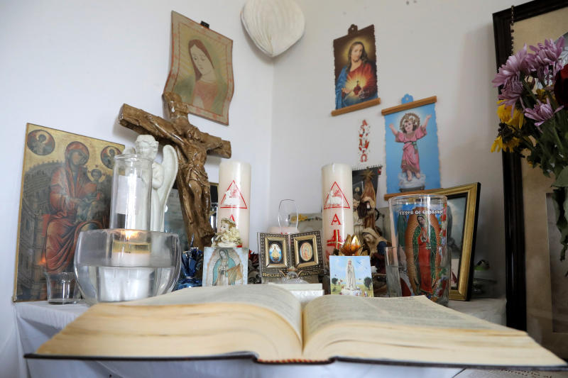 FILE - In this Thursday, May 14, 2020, an opened Bible is seen on a table next to religious items at a crab house where guest migrant workers from Mexico live in Fishing Creek, Md. More than a thousand Mexican immigrants have died of the virus in the U.S., according to the Mexican government, and many of their families are struggling to bring dead loved ones home. (AP Photo/Julio Cortez, File)