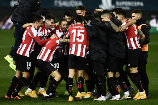 Athletic Bilbao players jubilate at the end of the Spanish Super Cup semi final soccer match between Real Madrid and Athletic Bilbao at La Rosaleda stadium in Malaga, Spain, Thursday, Jan. 14, 2021. Athletic Bilbao won 2-1 and will play the final. (AP Photo/Jose Breton)