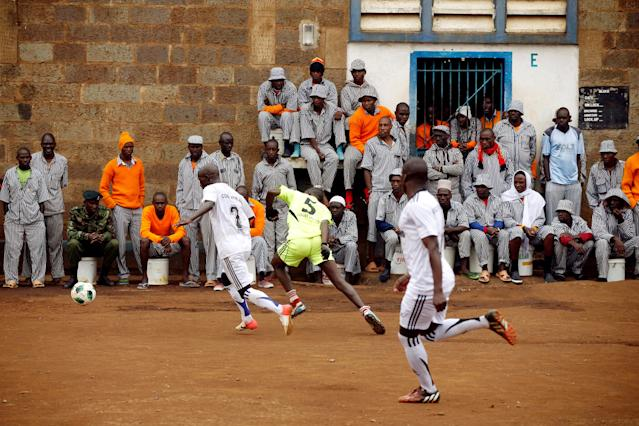 <p>Kenyan prisoners watch a mock World Cup soccer match between Russia and Saudi Arabia during a monthlong soccer tournament involving eight prison teams at the Kamiti Maximum Security Prison, Kenya's largest prison facility, near Nairobi, on June 14, 2018. (Photo: Baz Ratner/Reuters) </p>