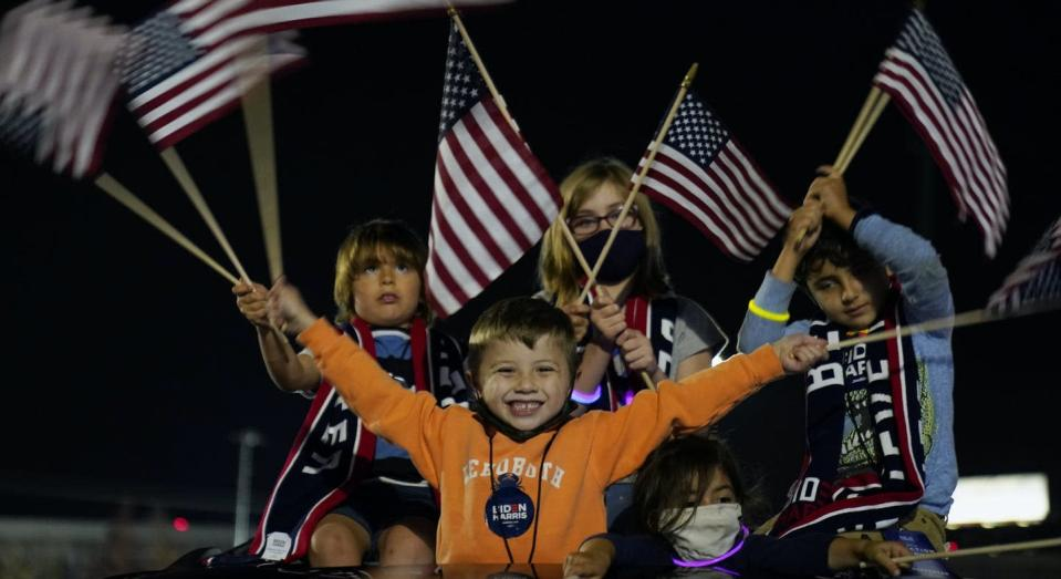 """<span class=""""caption"""">Children wave American flags before an event with President-elect Joe Biden in November 2020, in Wilmington, Del. </span> <span class=""""attribution""""><span class=""""source"""">(AP Photo/Andrew Harnik)</span></span>"""