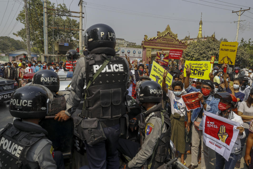 Police stand guard as demonstrators protest against the military junta's arrest and chagrining of National League for Democracy party lawmakers, Mandalay region Chief Minister Zaw Myint Maung & Mayor Ye Lwin outside Aung Myay Thar Zan Township court in Mandalay, Myanmar on Thursday, Feb. 18, 2021. Tens of thousands of demonstrators flooded the streets of Myanmar's biggest city Wednesday, in one of largest protests yet of a coup, despite warnings from a U.N. human rights expert that recent troop movements could indicate the military was planning a violent crackdown. (AP Photo)