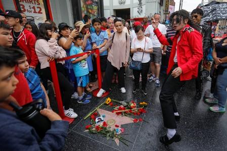 A Michael Jackson impersonator dances next to Michael Jackson's star on the Hollywood Walk of Fame ten years after the death of child star turned King of Pop in Los Angeles, California