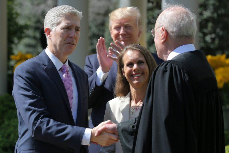Gorsuch shakes hands with Justice Anthony Kennedy after being sworn as his wife, Louise Gorsuch, and President Trump look on. (Carlos Barria/Reuters)