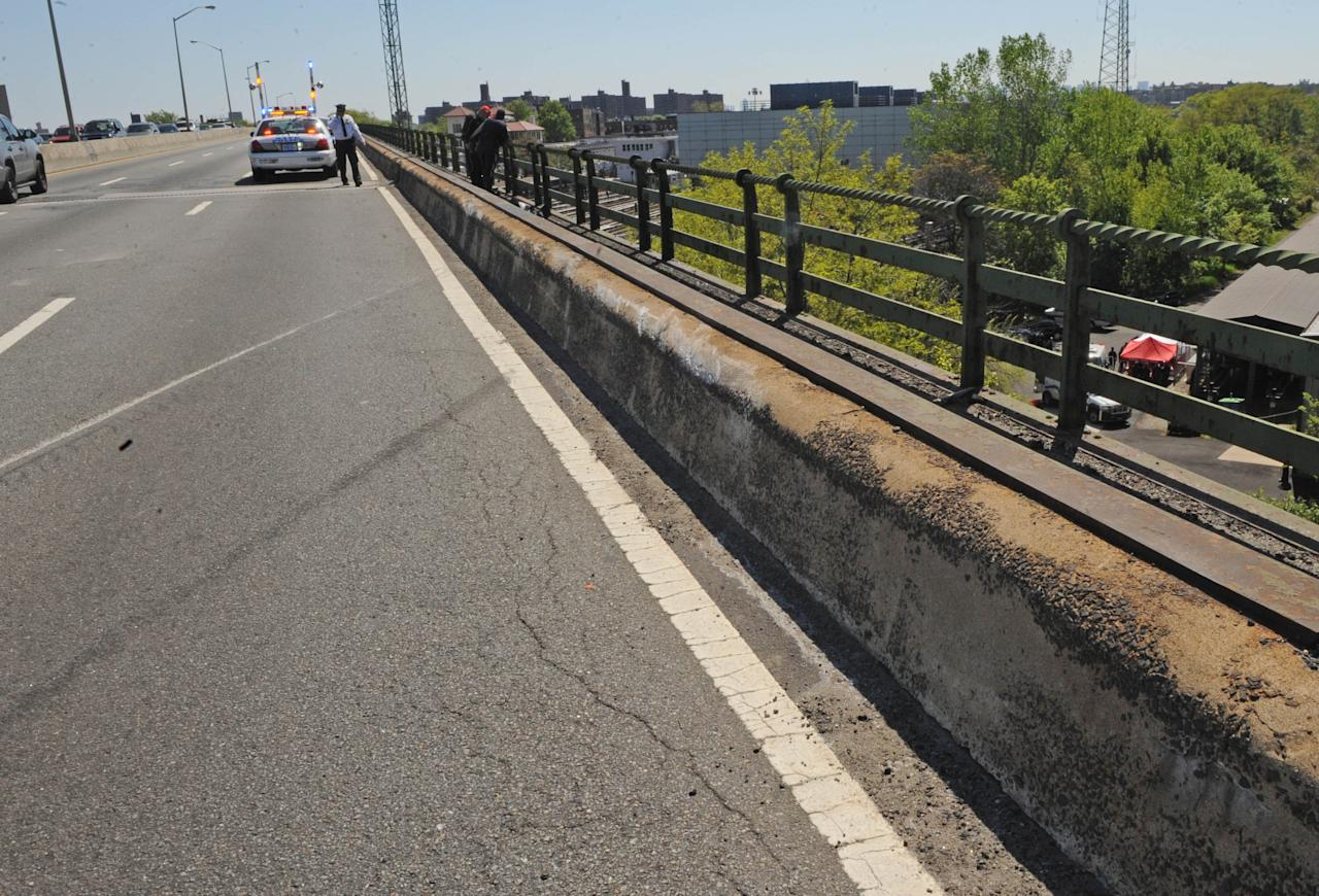 Skid marks and a scraped concrete barrier mark the spot where a van carrying seven occupants plunged off the highway to a wooded area below, Sunday April 29, 2012, in New York. Authorities say the out-of-control van plunged off a roadway near the Bronx Zoo, killing seven people, including three children. (AP Photo/ Louis Lanzano)