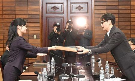 South Korean singer and chief delegate Yun Sang exchanges documents with Hyon Song Wol, head of the Samjiyon Orchestra, during their meeting at the truce village of Panmunjom, North Korea, March 20, 2018. The Unification Ministry/Yonhap via REUTERS