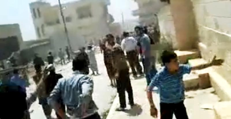 In this image made from amateur video released by the Shaam News Network and accessed Tuesday, May 15, 2012, purports to show Syrians running from gun shots in Khan Sheikhoun, Idlib, Syria. A team of international observers were evacuated Wednesday from a tense town in northern Syria a day after their convoy was hit by a roadside bomb, a U.N. spokesman said. The team's vehicles were struck by the blast Tuesday during a mission in the northern town of Khan Sheikhoun. (AP Photo/Shaam News Network via AP video) TV OUT, THE ASSOCIATED PRESS CANNOT INDEPENDENTLY VERIFY THE CONTENT, DATE, LOCATION OR AUTHENTICITY OF THIS MATERIAL