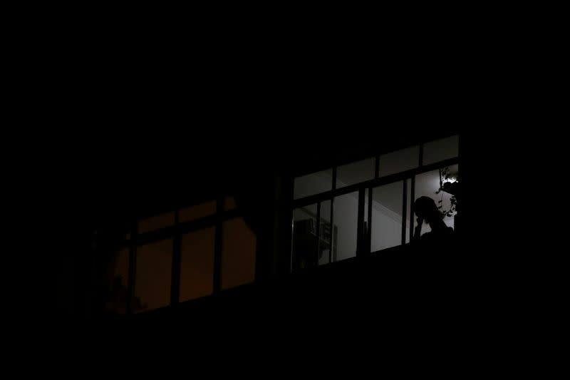 A demonstrator hits a pot from the window of his home to protest against Brazilian President Jair Bolsonaro's televised speech, during the outbreak of the coronavirus disease (COVID-19), in Sao Paulo