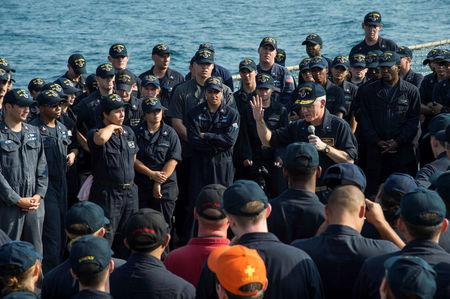 Handout photo of U.S. Navy Rear Admiral Jim Malloy, commander, Task Force 50, speaks to the crew of the guided-missile destroyer USS Hopper on the ship's flight deck at sea in the Arabian Gulf