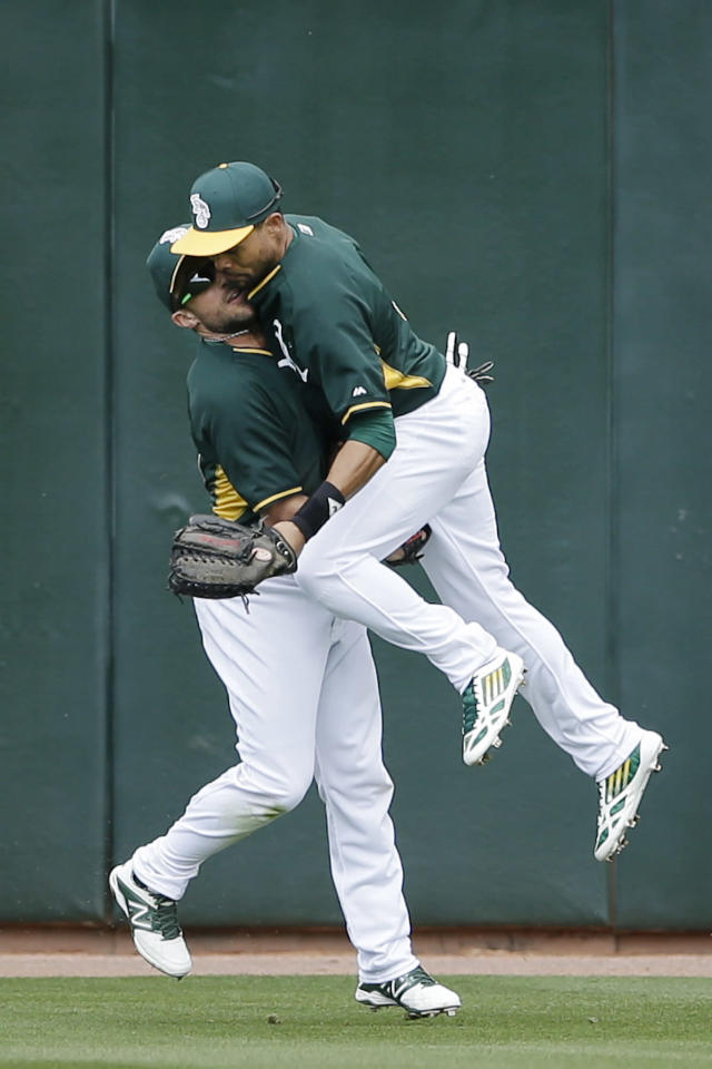 Oakland Athletics center fielder Coco Crisp, right, collides with left fielder Sam Fuld as he chases down a hit for a double by the Milwaukee Brewers' Jean Segura during the second inning of a spring training baseball game, Thursday, Feb. 27, 2014, in Scottsdale, Ariz. (AP Photo/Gregory Bull)