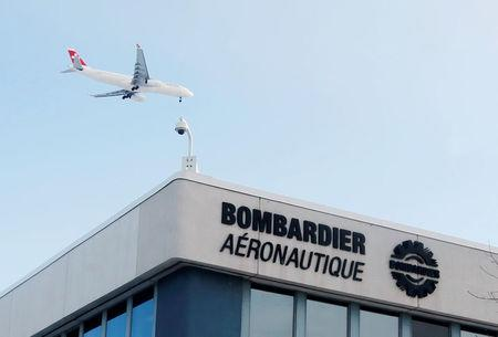FILE PHOTO:  A plane flies over a Bombardier plant in Montreal, Quebec, Canada on January 21, 2014.   REUTERS/Christinne Muschi/File Photo