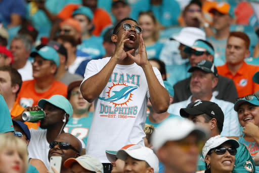 FILE - In this Sunday, Sept. 29, 2019 file photo, a Miami Dolphins fan yells, during the first half at an NFL football game against the Los Angeles Chargers, in Miami Gardens, Fla. The Miami Dolphins NFL football team has decided to allow up to 13,000 socially distancing fans to attend their home opener against the Buffalo Bills on Sept 20, with the approval of state and local political leaders. (AP Photo/Wilfredo Lee, File)