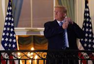 Then-US President Donald Trump takes off his facemask on October 5, 2020 as he arrives at the White House upon his return from Walter Reed Medical Center, where he underwent treatment for Covid-19, in Washington, DC
