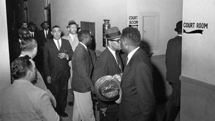 Lawyers proceed into the court room at the Richland County Court House for the case against James Edwards Jr., et al. Edwards and others were arrested for breach of peace following civil rights demonstrations they conducted at the S.C. State House on March 2, 1961. Pictured here are several defendants along with attorneys Matthew Perry, wearing glasses, and Lincoln C. Jenkins, in hat and overcoat. State N.A.A.C.P president J. Arthur Brown, with hand raised to his breast pocket, is also in the group.