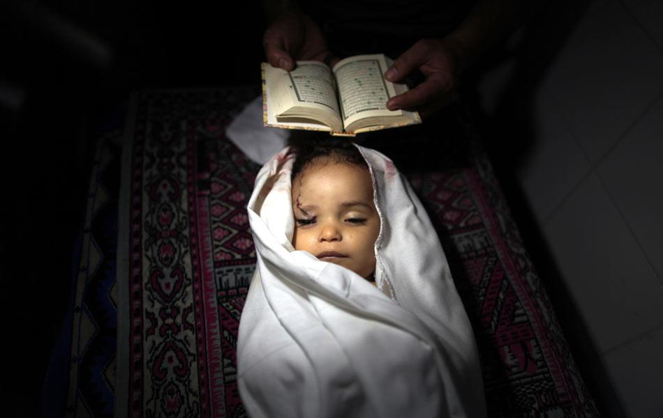 A Palestinian mourner prays over the body of Hadeel al-Hadad, a two-year-old girl, during her funeral in Gaza City, on June 20, 2012. According to Palestinian medics, Hadad died in an unexplained explosion, with the Israeli military spokesman denying any air strike in the area at the time during tit-for tat strikes by Palestinian militants firing rockets into Israel and the Israeli military carrying out air strikes. AFP PHOTO/MAHMUD HAMS