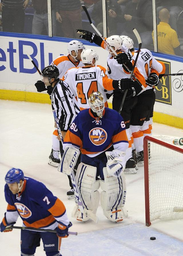 Philadelphia Flyers' Vincent Lecavalier (40), second from left, background, celebrates his second goal in the first period with teammates as New York Islanders' Matt Carkner (7) and goalie Kevin Poulin (60) react in an NHL hockey game at the Nassau Coliseum on Saturday, Oct. 26, 2013, in Uniondale, N.Y. (AP Photo/Kathy Kmonicek)