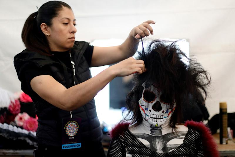 A woman gets make-up before taking part in a procession to commemorate Day of the Dead in Mexico City on Saturday.