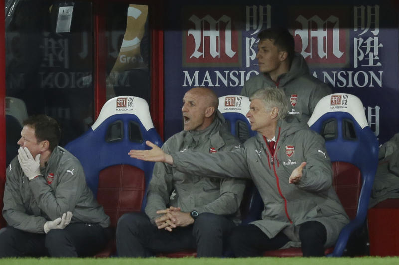 Arsenal manager Arsene Wenger, right, gestures to the pitch during the English Premier League soccer match between Crystal Palace and Arsenal at Selhurst Park in London, Monday April 10, 2017. (AP Photo/Tim Ireland)