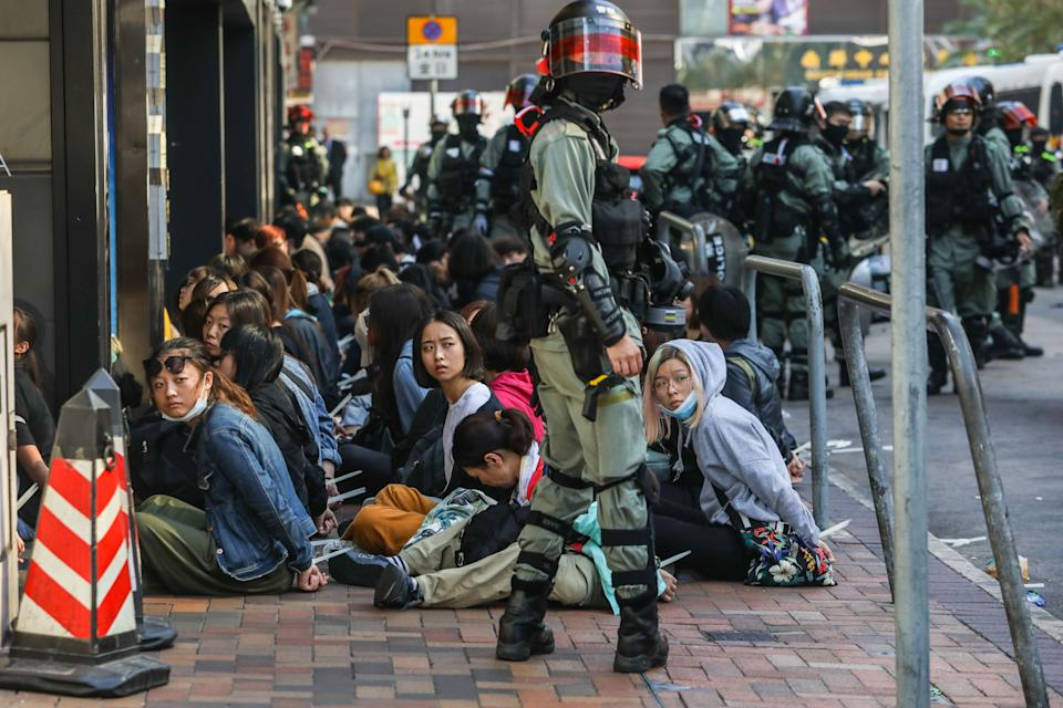People are detained by police near the Hong Kong Polytechnic University in Hung Hom district of Hong Kong on November 18, 2019. - Pro-democracy demonstrators holed up in a Hong Kong university campus set the main entrance ablaze November 18 to prevent surrounding police moving in, after officers warned they may use live rounds if confronted by deadly weapons. (Photo by DALE DE LA REY / AFP) (Photo by DALE DE LA REY/AFP via Getty Images)
