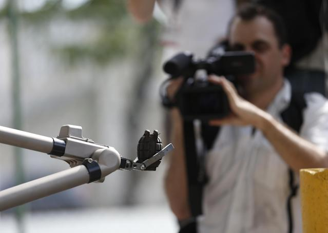 A cameraman films a robot holding a hand grenade during a media presentation to show a slice of Brazilian police force security training for the 2014 World Cup and 2016 Olympics, in Rio de Janeiro, Brazil, Tuesday, Dec. 3, 2013. Brazil's police are getting training from their French counterparts. Security is on the agenda as football's world governing body FIFA meets in the run-up to Friday's World Cup draw. (AP Photo/Silvia Izquierdo)