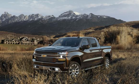 A dark gray 2019 Chevrolet Silverado pickup, parked in a field with mountains in the background.