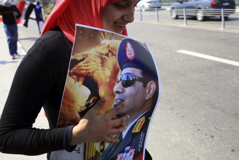 FILE - In this Oct. 6, 2013 file photo, an Egyptian carries a portrait of Defense Minister Gen. Abdel-Fattah el-Sissi for the 40th anniversary of Egypt's Oct. 6 crossing of the Suez Canal during the 1973 war with Israel, while celebrating on a bridge leading to Tahrir Square in Cairo. In an audiotape, the military chief talks about his dreams, saying that in one nighttime vision he was brandishing a sword and that in another he told the late Anwar Sadat that he himself would be president one day. The tape, apparently leaked by opponents to embarrass the general, kicked off an online storm of parodies and mockery. But to most Egyptians, among whom dream interpretation is commonplace, it only deepened an image of the country's most powerful figure and very possibly its next president as a spiritual man, in touch with the nation's traditions. (AP Photo/Thomas Hartwell, File)