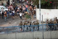 Lebanese army take cover behind shields as they deploy during a protest after Lebanese Prime Minister-Designate Saad al-Hariri abandoned his effort to form a new government, in Beirut